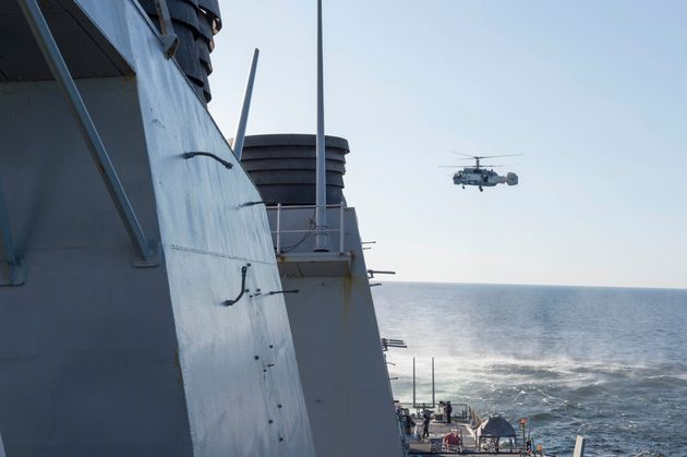 A Russian Kamov KA-27 HELIX helicopter flies low-level passes near the Arleigh Burke-class guided missile...