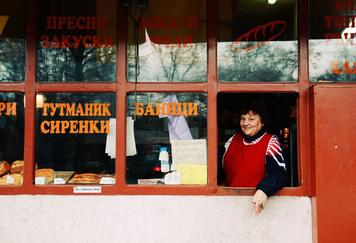 Shop-keeper at a small bakery in downtown Sofia, Bulgaria, inviting customers with a smile.