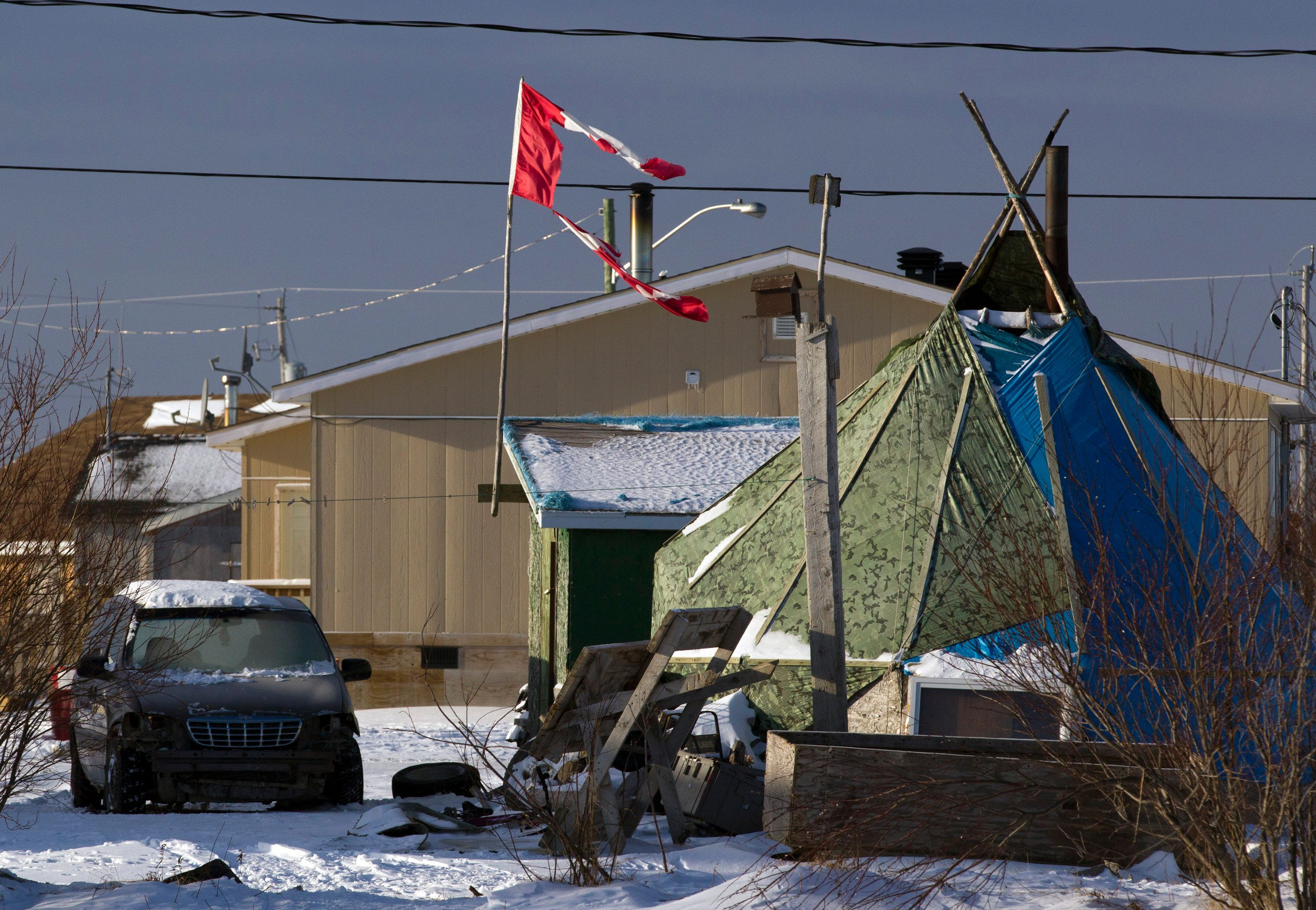 A tattered Canadian flag flies over a teepee in Attawapiskat, Ontario, December 17, 2011. About 20 families will move into a temporary shelter on December 23 to escape the housing crisis at the aboriginal reserve of Attawapiskat where many households live without running water or sanitary facilities, according to local media.    REUTERS/Frank Gunn/Pool  (CANADA - Tags: SOCIETY)