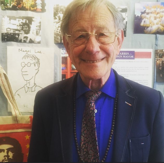 Harris poses next to a cartoon drawing of him as