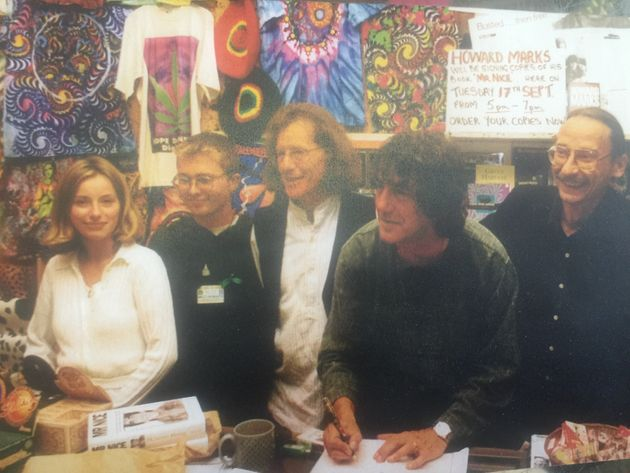 Howard Marks signs copies of his book, next to Harris,