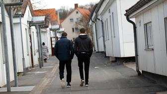 Migrants stroll between barracks at the camp for refugees in Friedland, Germany April 4, 2016.  REUTERS/Kai Pfaffenbach