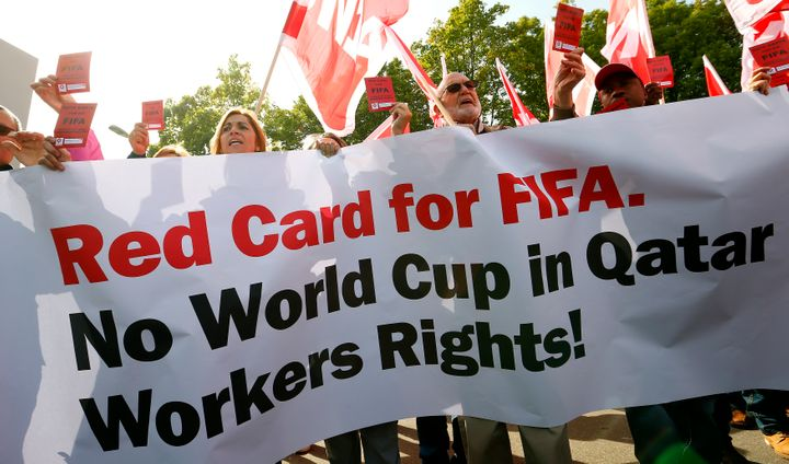 Protesters challenge FIFA to respect the rights of migrant workers in Qatar outside the organization's headquarters in Zurich