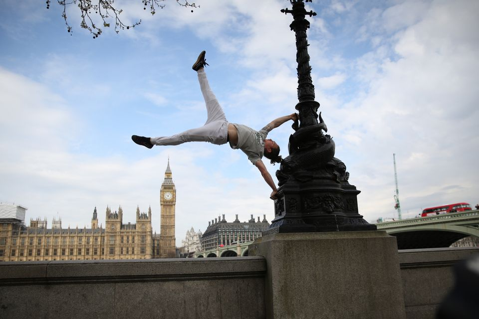 British Parkour expert Tim Shieff performs a hand-stand in front of the House of Commons, as he launches...