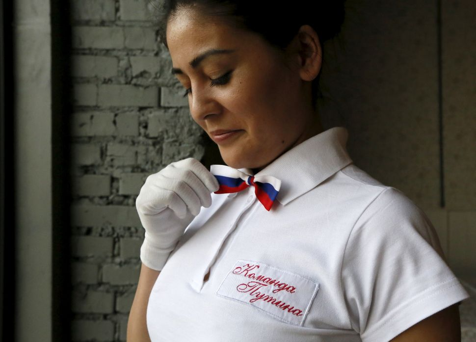 A waitress straightens a bow tie in the colors of the Russian national flag.