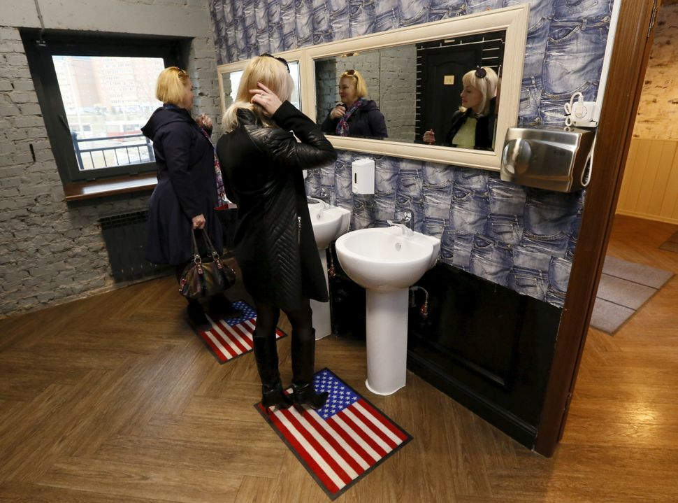 Visitors stand on rugs depicting the U.S. flag in the President Cafe's bathroom.