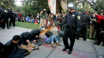 """A University of California Davis police officer pepper-sprays students during their sit-in at an """"Occupy UCD"""" demonstration in Davis, California November 18, 2011.  UC Davis Chancellor Linda Katehi apologized to jeering students on November 21 for police use of pepper spray against campus protesters in a standoff captured by video and widely replayed on television and the Internet. Faculty and student critics of Friday's confrontation, some of whom demanded the chancellor's resignation, said it had damaged the school's image and the climate for free expression at the university. Photo taken November 18, 2011.  REUTERS/Brian Nguyen  (UNITED STATES - Tags: CIVIL UNREST EDUCATION CRIME LAW TPX IMAGES OF THE DAY)"""