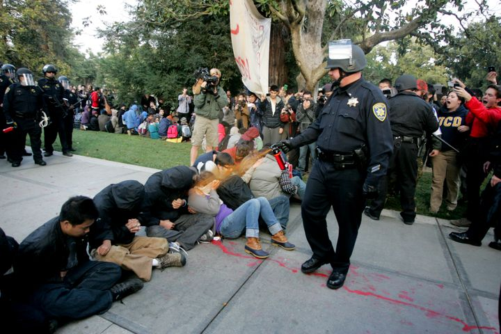 """A University of California Davis police officer pepper-sprays students during their sit-in at an """"Occupy UCD"""" demonstration i"""