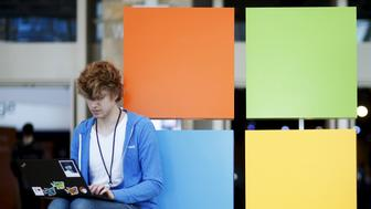 An attendee works next to the Microsoft logo during the Microsoft Build 2016 Developers Conference in San Francisco, California March 30, 2016. REUTERS/Beck Diefenbach