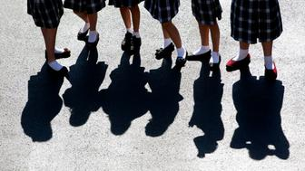 Low angle view of junior high school girls at a Catholic school on a playground.