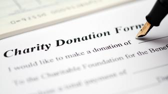 Making a donation to charity. Cheque book and donation form with a pen. Selective focus