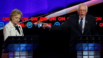 Democratic U.S. presidential candidate Senator Bernie Sanders (R) gestures towards rival Hillary Clinton as he speaks during a Democratic debate hosted by CNN and New York One at the Brooklyn Navy Yard in New York April 14, 2016. REUTERS/Lucas Jackson