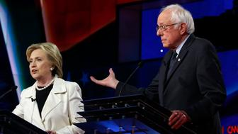 Democratic U.S. presidential candidate Hillary Clinton (L) speaks as rival candidate Senator Bernie Sanders gestures during a Democratic debate hosted by CNN and New York One at the Brooklyn Navy Yard in New York April 14, 2016. REUTERS/Lucas Jackson