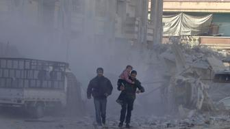 A man carries a girl past damage at a site hit by what activists said was an air strike by forces loyal to Syria's President Bashar al-Assad in the northwestern Homs district of Al Waer December 30, 2014. REUTERS/Stringer   (SYRIA - Tags: CIVIL UNREST CONFLICT)