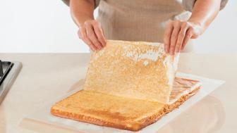 Woman carefully removing wax paper from flat rectangle of baked sponge cake on kitchen worktop