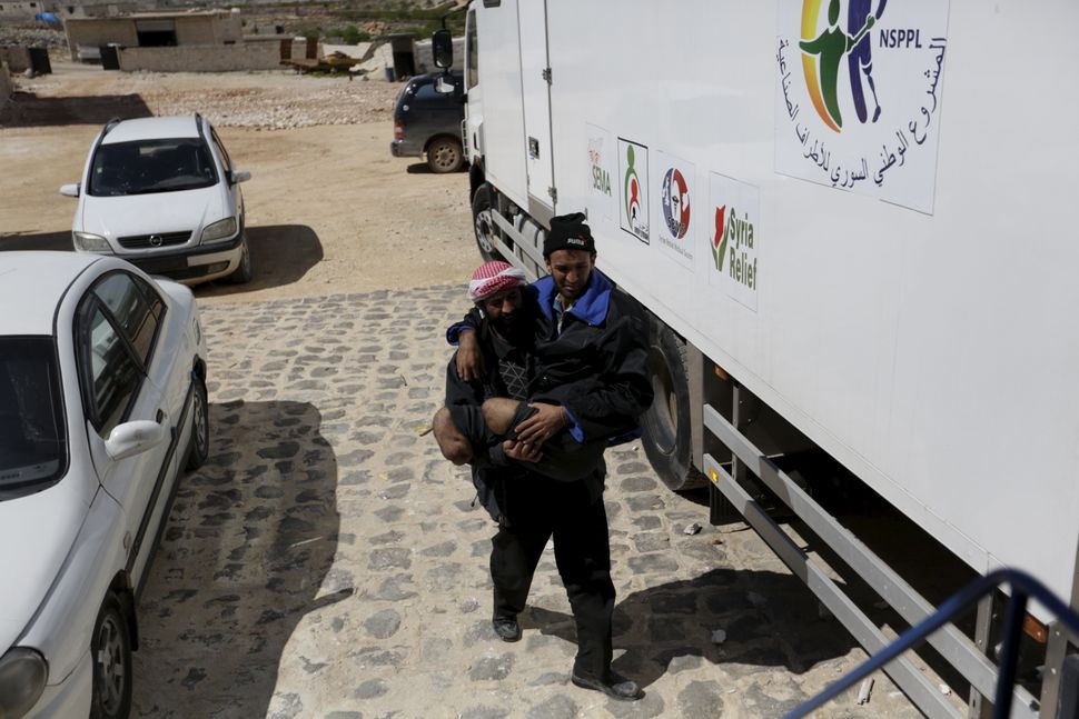 A man carries his brother, whose legs had been amputated, to the mobile clinic in Maaret al-Numan.