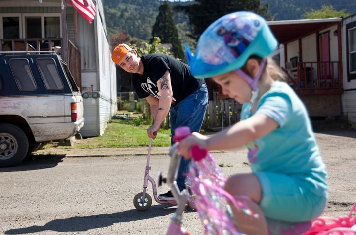 Bryan Thouvenel rides on a scooter while watching his daughter Harmony, 5, on her bike in front of their house in Myrtle Cree