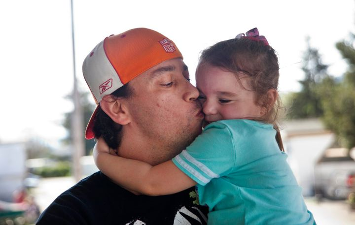 Bryan Thouvenel gives his daughter Harmony, 5, a kiss while standing for a portrait in front of their home in Myrtle Creek, S