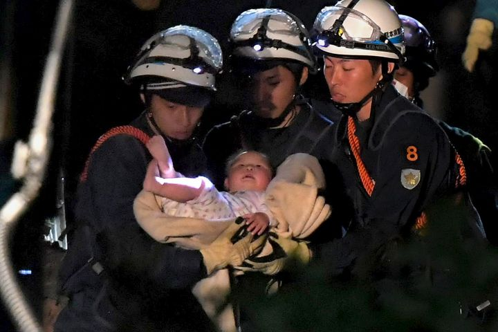 An eight-month-old baby is carried away by rescue workers after being rescued from her collapsed home caused by an earthquake