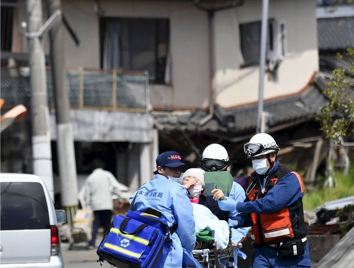 An injured person is carried by rescuers near a damaged house caused by an earthquake in Mashiki town, Kumamoto prefecture, s