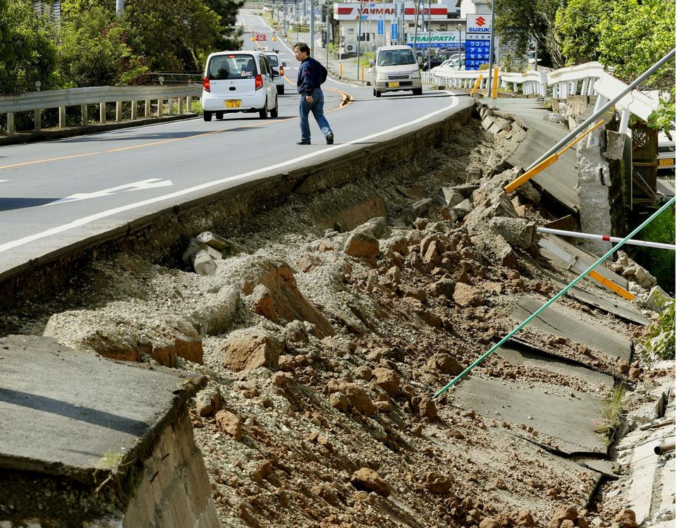 A man walks by a damaged road in Mashiki on April 15, one day after a deadly earthquake struck southern Japan.