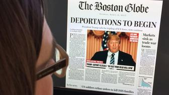 TOPSHOT - This April 10, 2016 photo taken in Washington shows a woman reading an online version of a mockup of what a frontpage might look like should Republican frontrunner Donald Trump win the presidency, as it condemned his 'deeply disturbing' and 'profoundly un-American' vision. 'Deportations to begin, President Trump calls for tripling of ICE (immigration and customs enforcement); riots continue,' read The Boston Globe's fake headline, dated April 9, 2017. It was posted on the editorial page, accompanied by a ruthless editorial article saying Trump's campaign 'demands an active and engaged opposition.'  / AFP / Karen BLEIER        (Photo credit should read KAREN BLEIER/AFP/Getty Images)