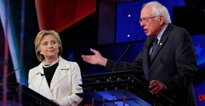 Democratic U.S. presidential candidate Hillary Clinton (L) listens to Sen. Bernie Sanders speak during a Democratic debate at the Brooklyn Navy Yard in New York April 14, 2016.