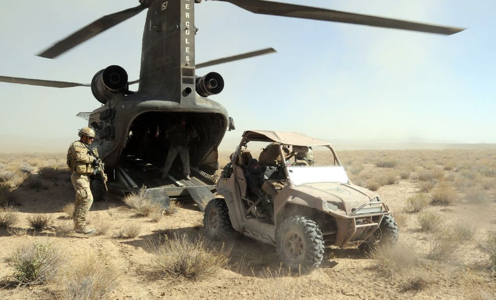 Soldiers with Special Operations Task Force-South load an all-terrain vehicle onto a CH-47 Chinook helicopter during operatio