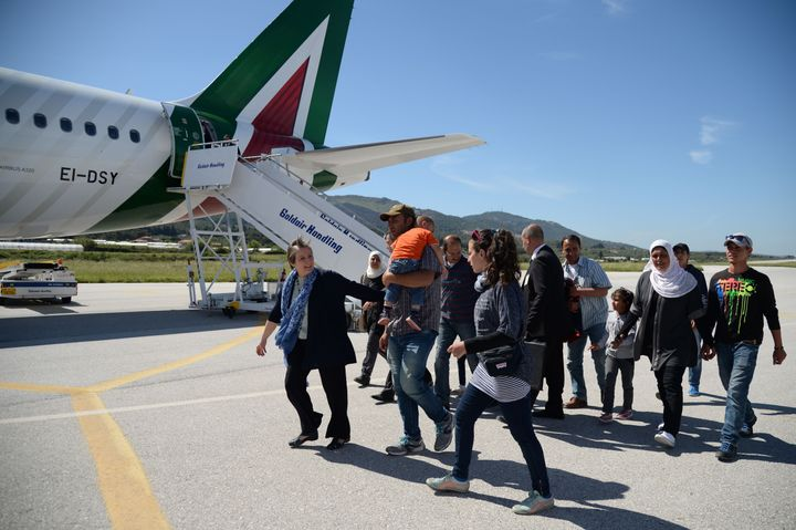 A group of Syrian refugees arrive to board a plane with Pope Francis on April 16, 2016 at the airport of Mytilene, in the Gre
