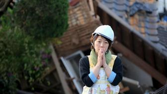 A woman reacts in front of collapsed house caused by an earthquake in Mashiki town, Kumamoto prefecture, southern Japan, in this photo taken by Kyodo April 16, 2016.  Mandatory credit REUTERS/Kyodo ATTENTION EDITORS - FOR EDITORIAL USE ONLY. NOT FOR SALE FOR MARKETING OR ADVERTISING CAMPAIGNS. THIS IMAGE HAS BEEN SUPPLIED BY A THIRD PARTY. IT IS DISTRIBUTED, EXACTLY AS RECEIVED BY REUTERS, AS A SERVICE TO CLIENTS. MANDATORY CREDIT. JAPAN OUT. NO COMMERCIAL OR EDITORIAL SALES IN JAPAN.      TPX IMAGES OF THE DAY