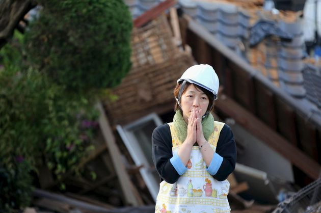 A woman reacts in front of collapsed house caused by an earthquake in Mashiki town. A 7.3 magnitude...