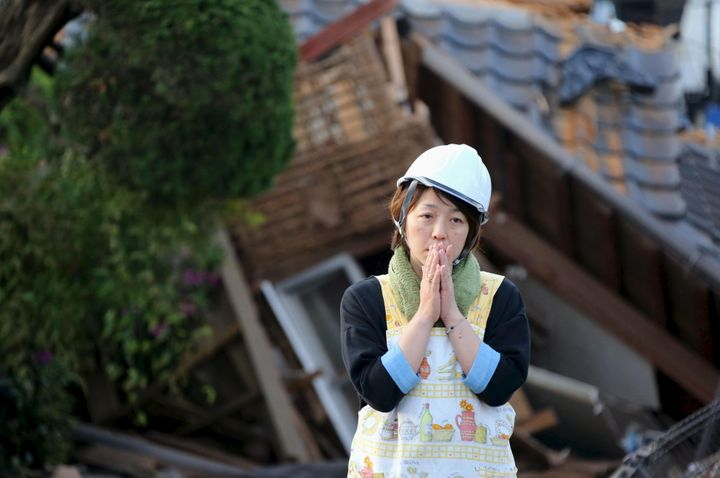 A woman reacts in front of collapsed house caused by an earthquake in Mashiki town. A 7.3 magnitude earthquake stru