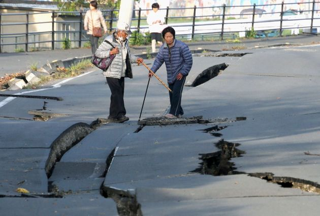 Local residents look at cracks caused by an earthquake on a road in Mashiki town. The USGS estimated...