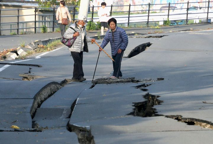 Local residents look at cracks caused by an earthquake on a road in Mashiki town. The USGS estimated that there was a 72