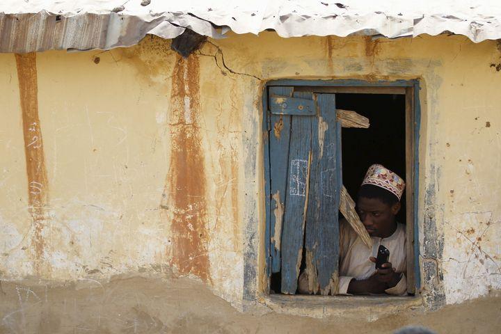 A boy looks through a broken window at a local Islamic school in Zaria, Kaduna state, Nigeria.Several former recruits d