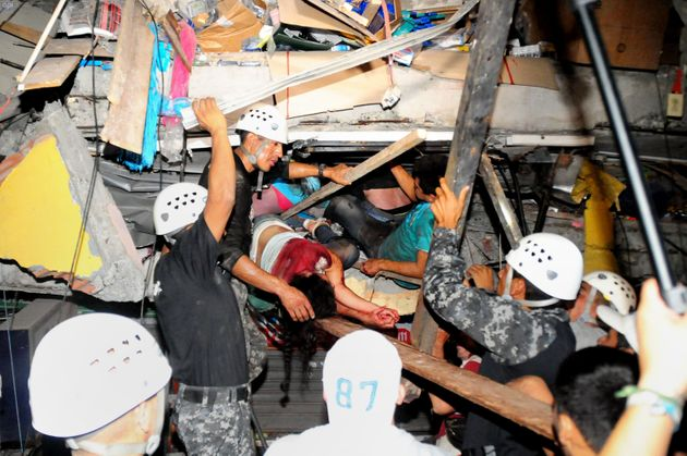 Rescue workers work to pull out survivors trapped in a collapsed building after a huge earthquake struck...