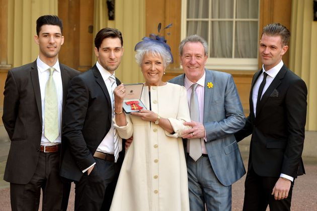 Lynda Bellingham holding her OBE with (left to right) sons Michael and Robert, husband Michael and step-son