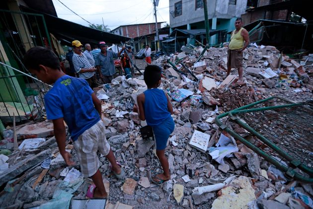 People stand amongst the rubble of fallen homes in Manta on April 17, 2016, after a powerful 7.8-magnitude...