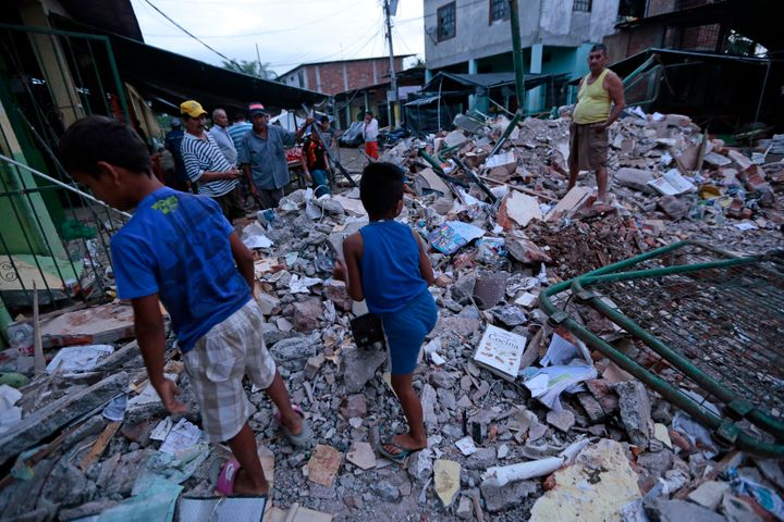 People stand amongst the rubble of fallen homes in Manta on April 17, 2016, after a powerful 7.8-magnitude earthquake struck