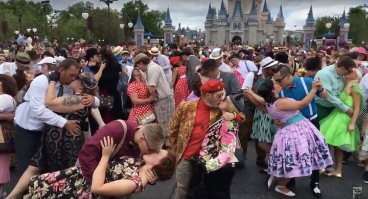 Couples pose in front ofthe Magic Kingdom's castle during Dapper Day on Saturday.