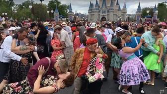 Couples are seen posing before the Magic Kingdom's castle during Dapper Day on Saturday.