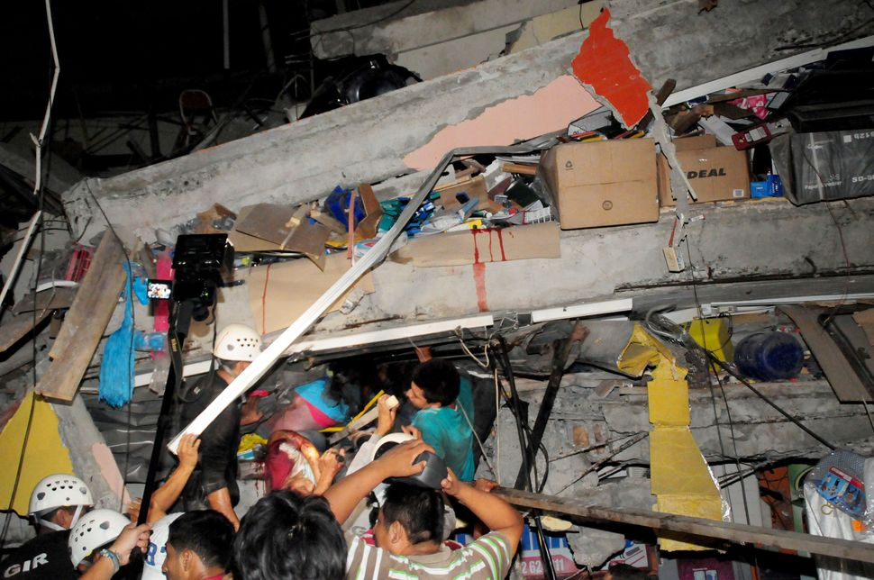Rescue workers work to pull out survivors trapped in a collapsed building after the huge earthquake struck, in the city