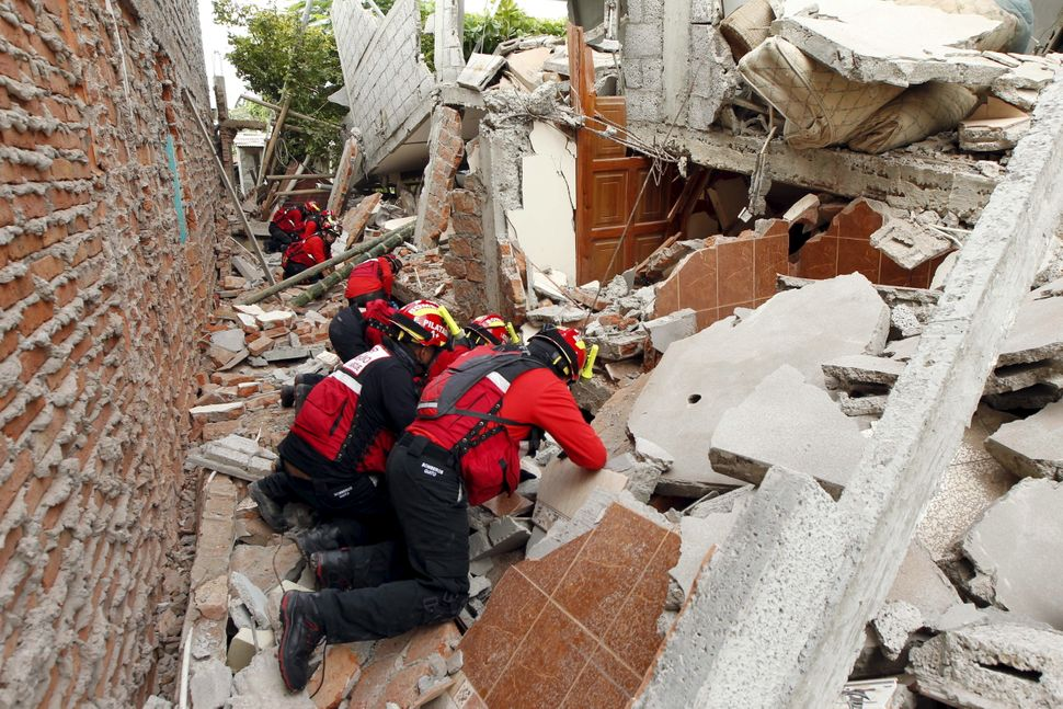 Firemen work after an earthquake struck off Ecuador's Pacific coast, in the Tarqui neighborhood in Manta on April 17, 2016.