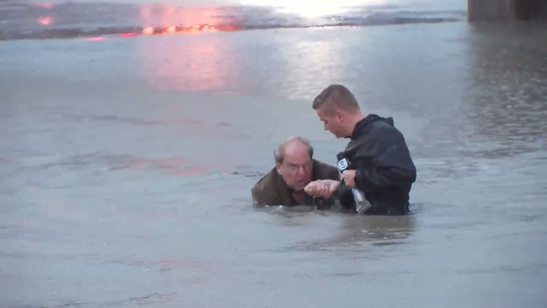 A local TV reporter is seen helping guide the driver out of the water and to higher ground.