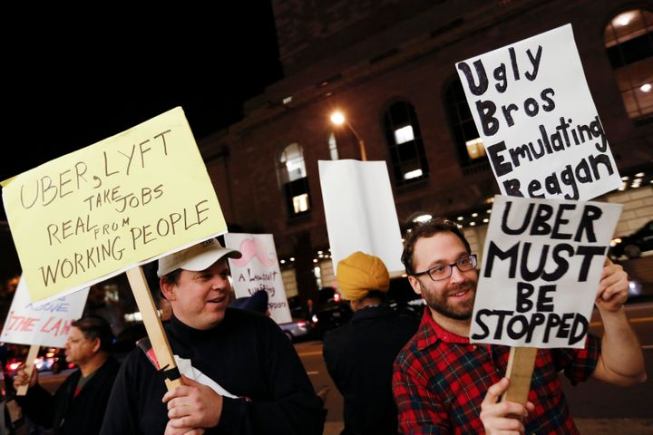 Demonstrators hold signs during a protest organized by the San Francisco Taxi Workers Alliance against ridesharing services U