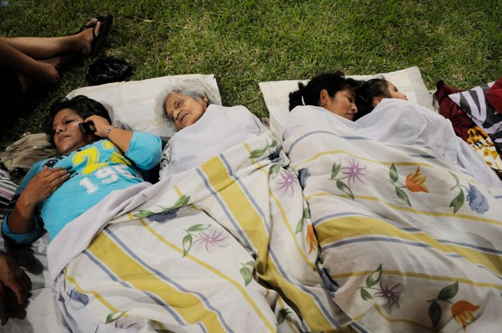 This picture shows people resting in a park after an earthquake in the city of Guayaquil on April 17, 2016.