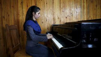 "Negin Ekhpulwak, leader of the Zohra orchestra, an ensemble of 35 women, practises on a piano at Afghanistan's National Institute of Music, in Kabul, Afghanistan April 9, 2016. Playing instruments was banned under Taliban rule in Afghanistan, and even today, many conservative Muslims frown on most forms of music. Living in an orphanage in the capital, Kabul, 19-year-old Negin leads an ensemble of 35 women that plays both Western and Afghan musical instruments. In a country notorious internationally for harsh restrictions on women in most areas of life, Negin's story highlights a double challenge. REUTERS/Ahmad Masood SEARCH ""ORCHESTRA KABUL"" FOR THIS STORY. SEARCH ""THE WIDER IMAGE"" FOR ALL STORIES TPX IMAGES OF THE DAY"