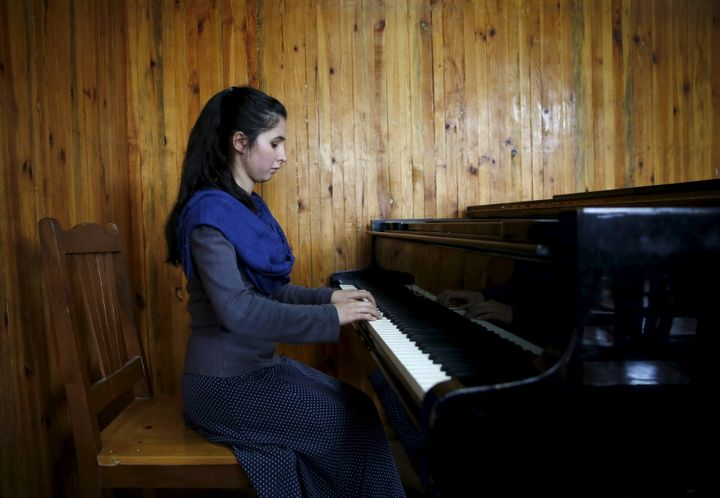 Negin Ekhpulwak, leader of the Zohra orchestra, an ensemble of 35 women, practises on a piano at Afghanistan's National Insti