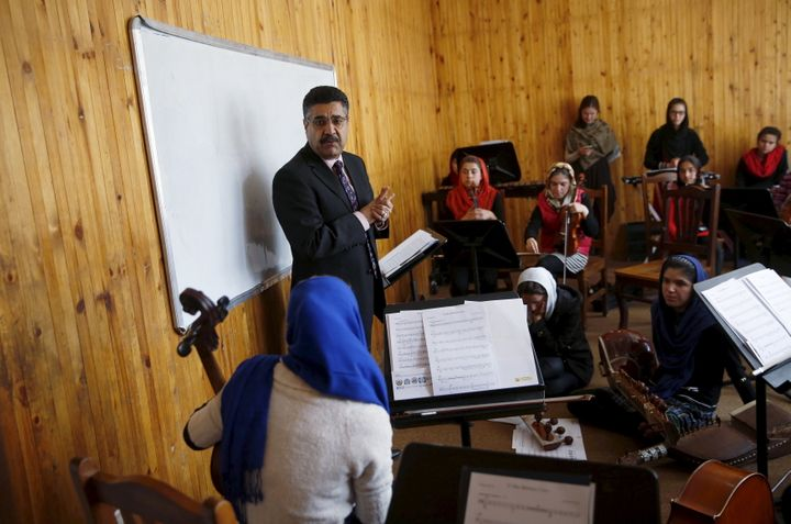 Ahmad Naser Sarmast, head of Afghanistan's National Institute of Music, speaks to members of the orchestra. Playing inst