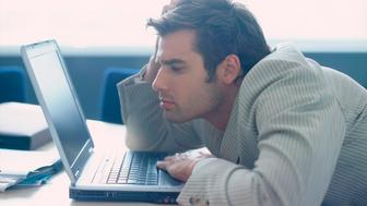 Businessman slouching in front of laptop
